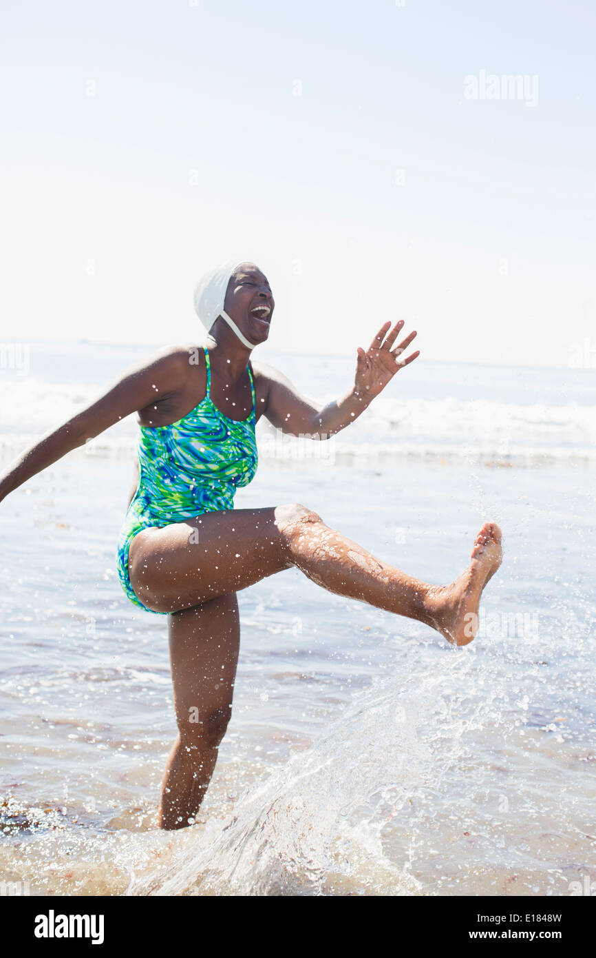 Woman splashing in ocean surf Photo Stock