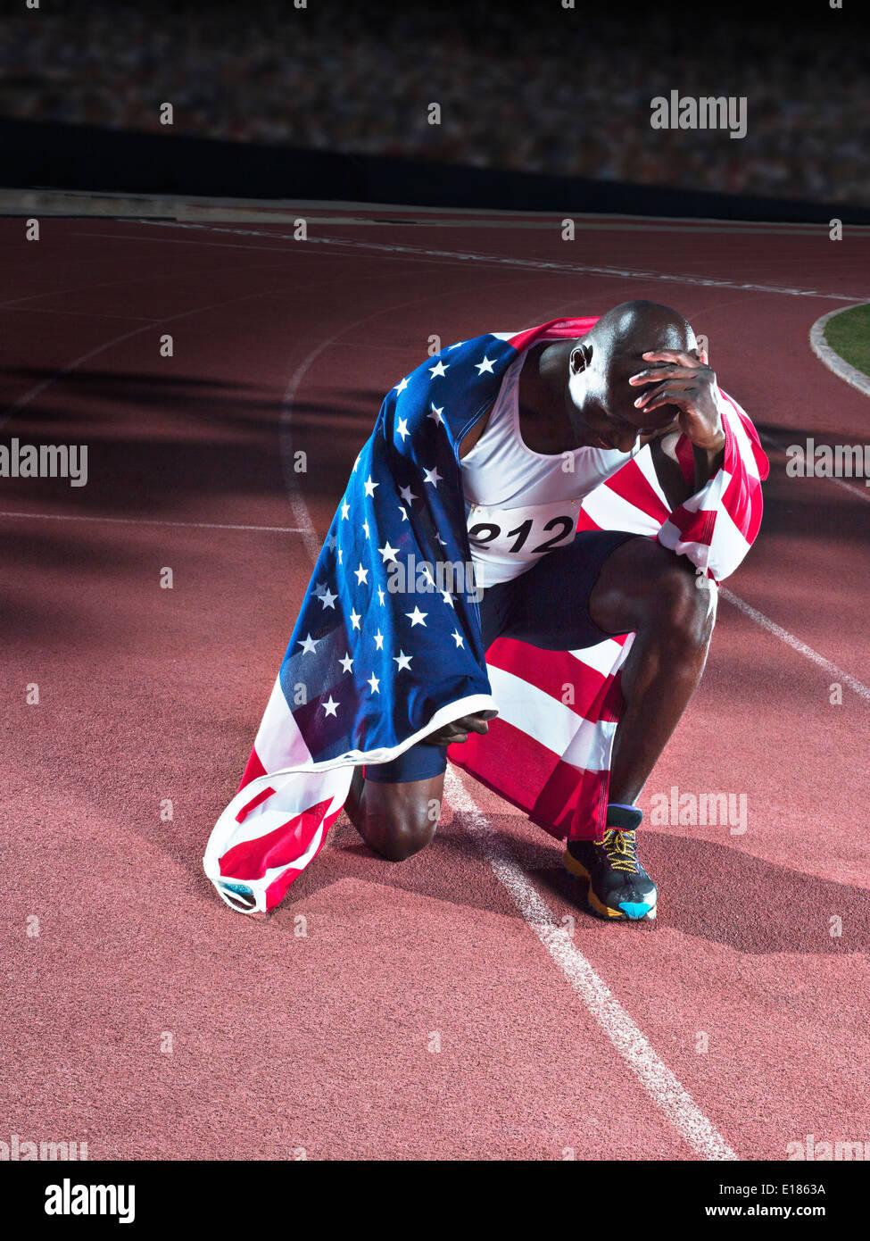Athlétisme enveloppé dans le drapeau américain sur la voie Photo Stock