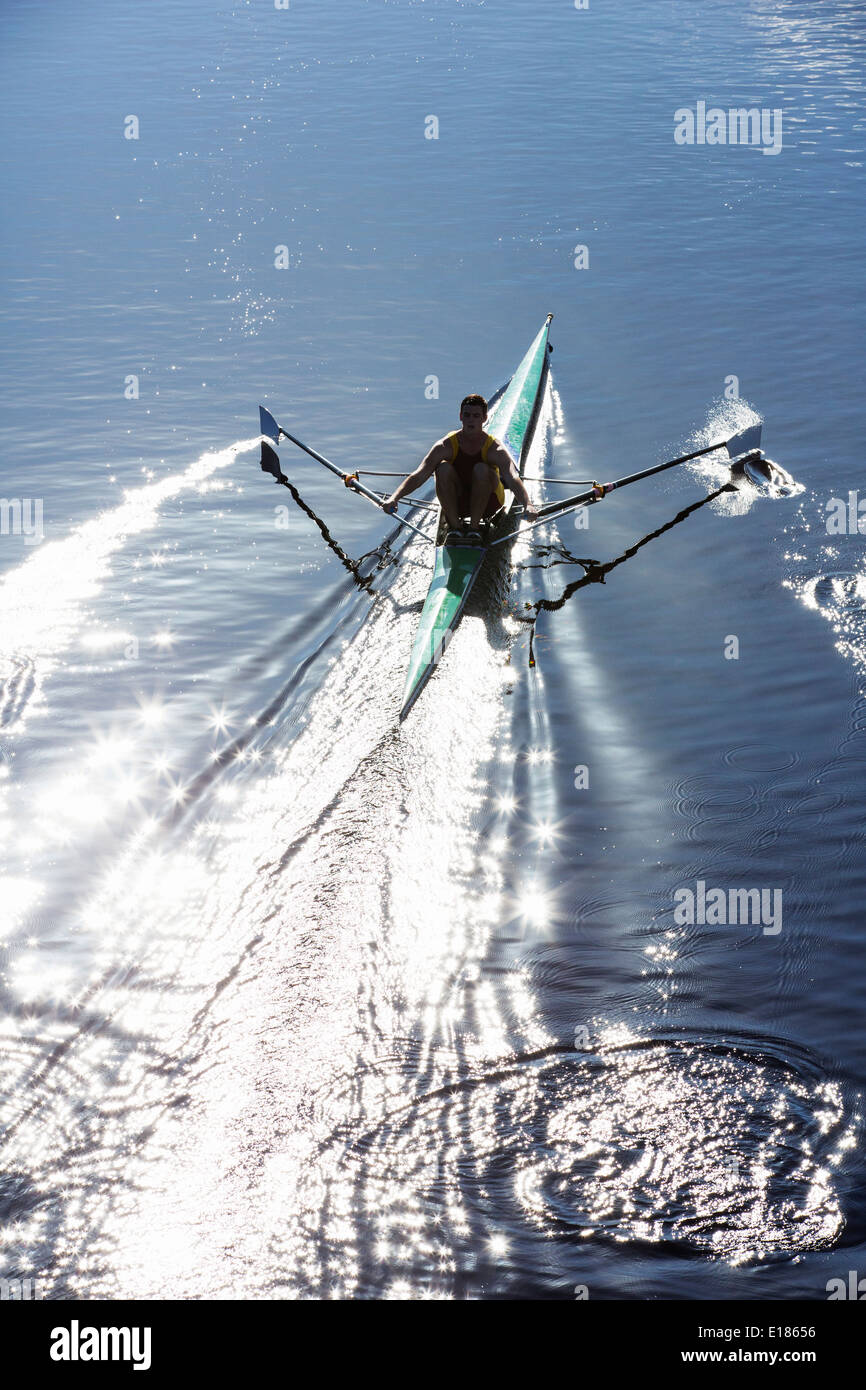 Man rowing scull on lake Photo Stock