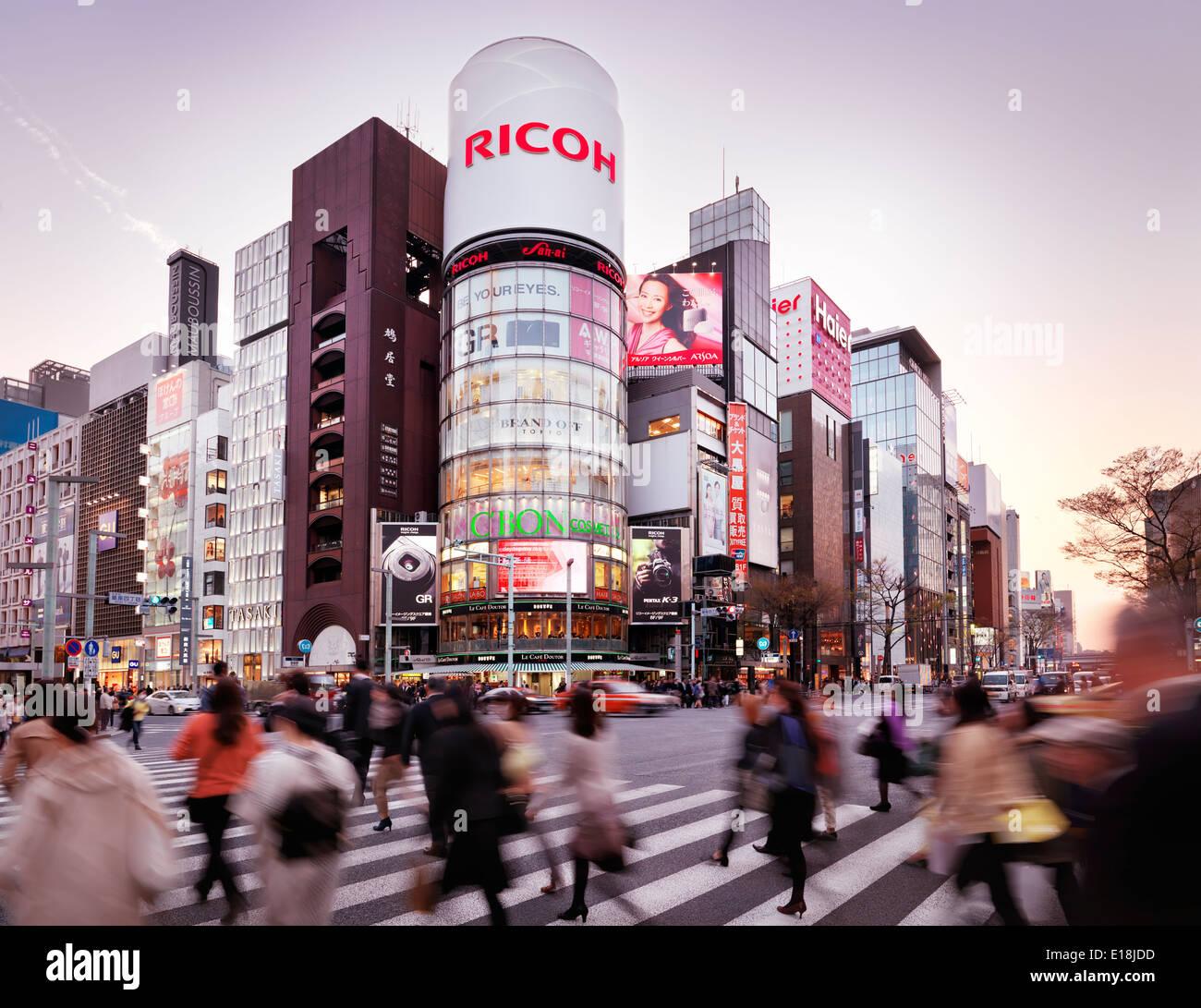 Les personnes qui traversent intersection de Harumi Dori et Chou Dori. Bâtiment de Ricoh au coucher du soleil. Ginza, Tokyo, Japon 2014. Photo Stock