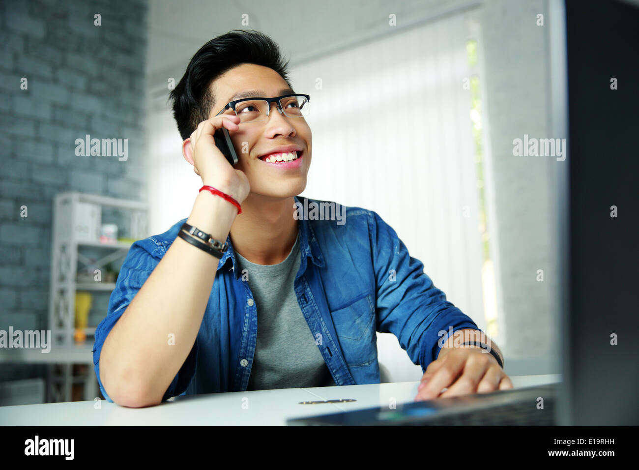 Young happy asian man talking on the phone sur son lieu de travail à Office Photo Stock