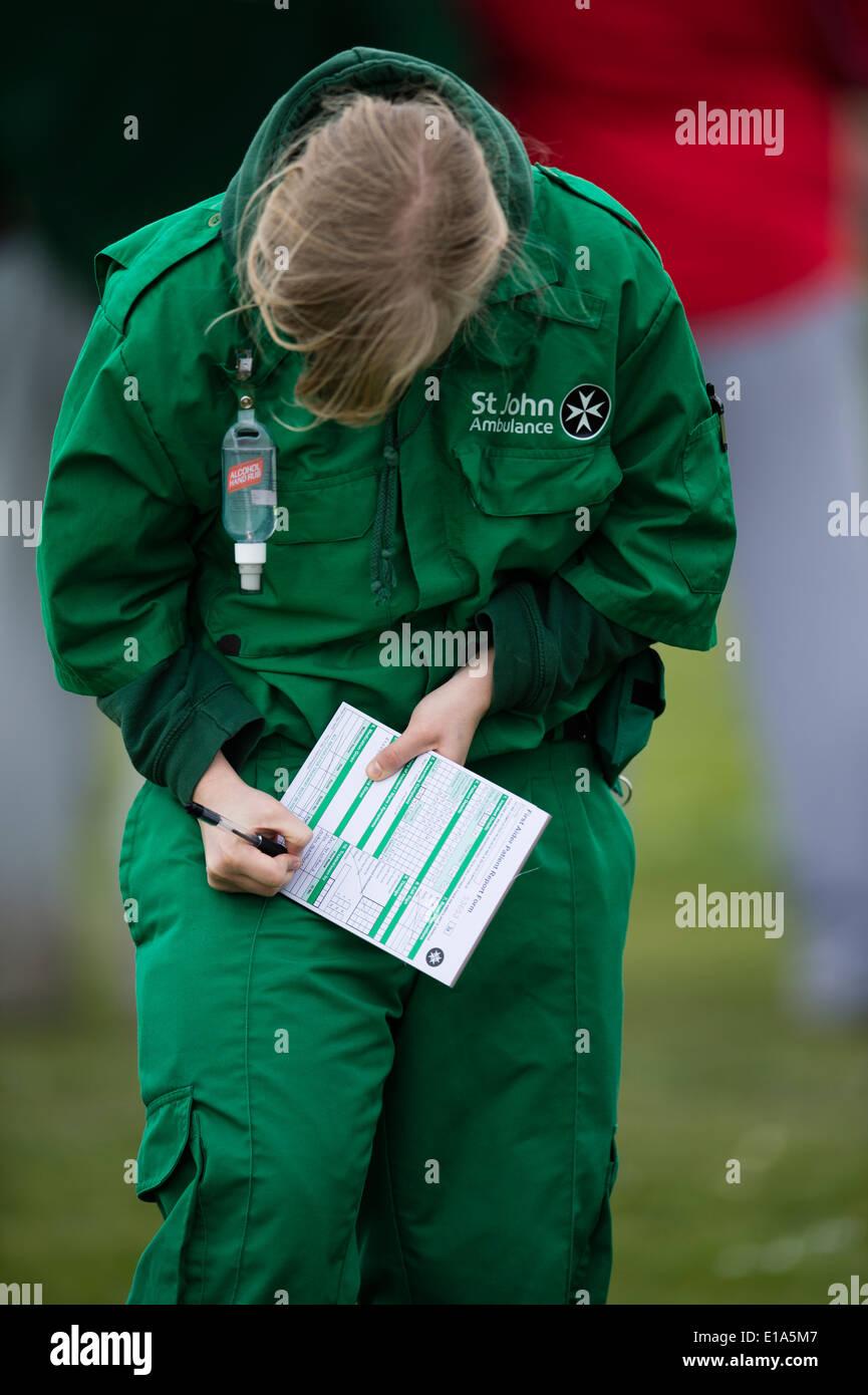 A St John Ambulance d'urgence bénévole secouriste personne chargée de remplir le formulaire de rapport du patient après le traitement de la personne Banque D'Images