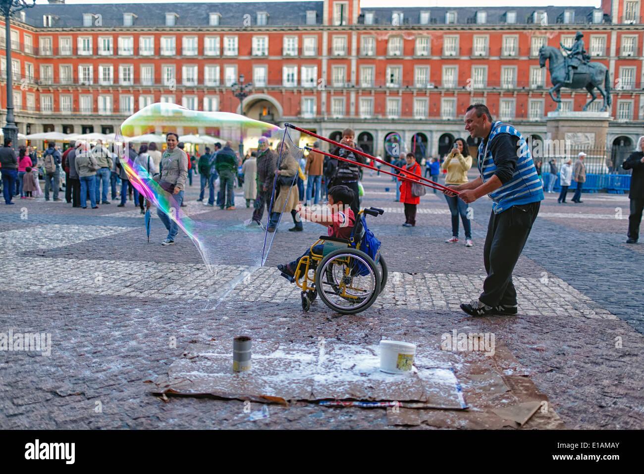 Bulle de savon enveloppant de l'artiste enfant handicapé dans un fauteuil roulant avec bulle de savon, la Plaza Mayor, Madrid, Espagne Photo Stock
