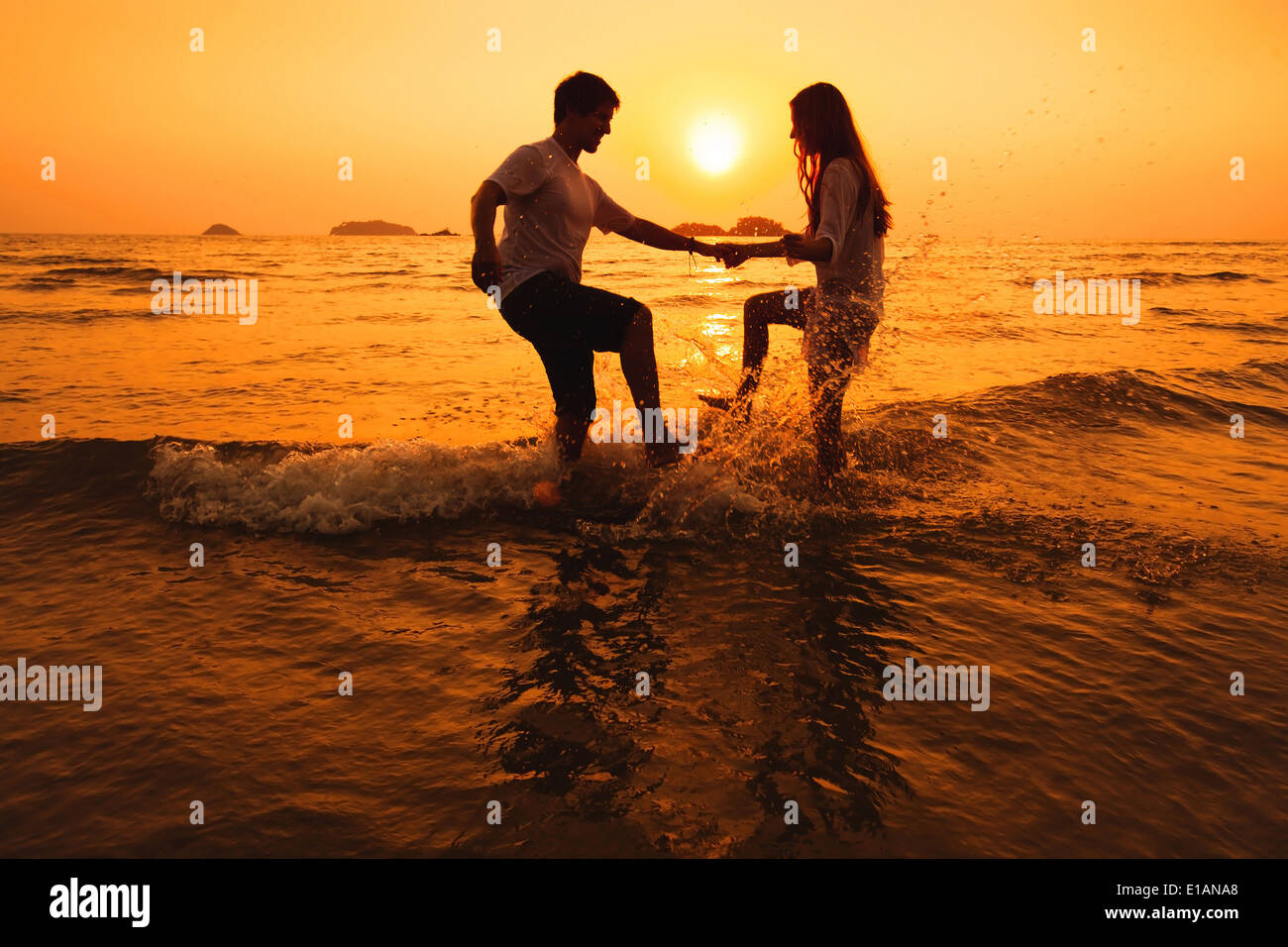 Couple having fun in the sea at sunset beach Photo Stock