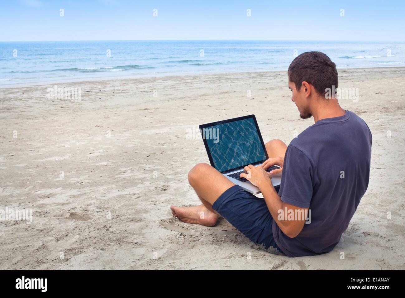L'homme à l'aide d'ordinateur avec internet sans fil sur la plage Photo Stock