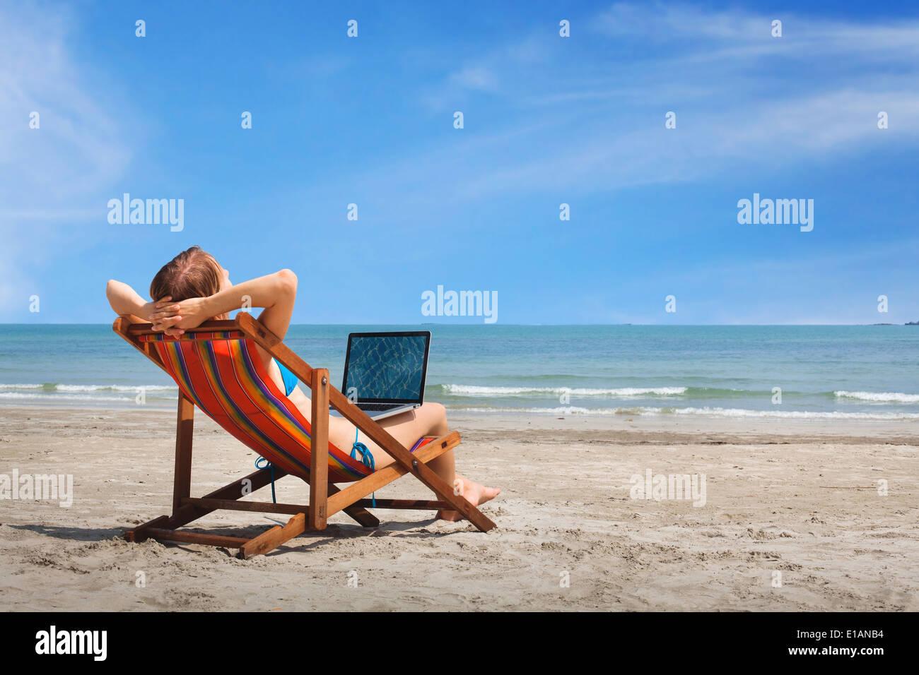 Femme heureuse avec un ordinateur portable sur la plage Photo Stock
