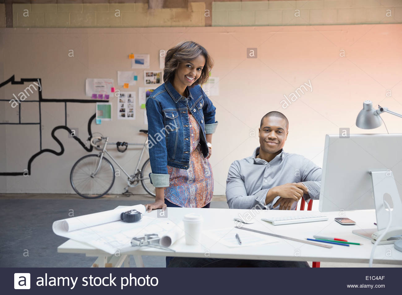 Portrait of business people at desk in office Photo Stock