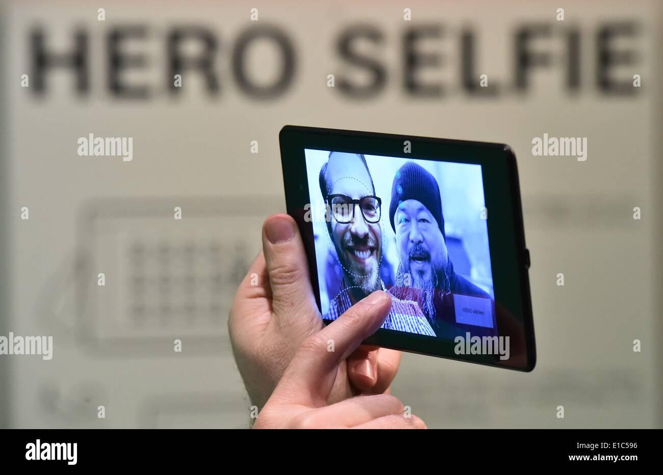 Neuhardenberg, Allemagne. 30 mai, 2014. Le co-créateur de l'exposition Boris Hars-Tschachotin est représenté à l'installation 'Hero' Selfies sur l'écran d'une tablette à côté de la photo de l'artiste Ai Weiwei en vue Neuhardenberg, Allemagne, 30 mai 2014. L'exposition 'Remebering le heros - 200 ans Neuhardenberg' (lit.) s'ouvre le 01 juin 2014. Photo: Patrick Pleul/dpa/Alamy Live News Photo Stock