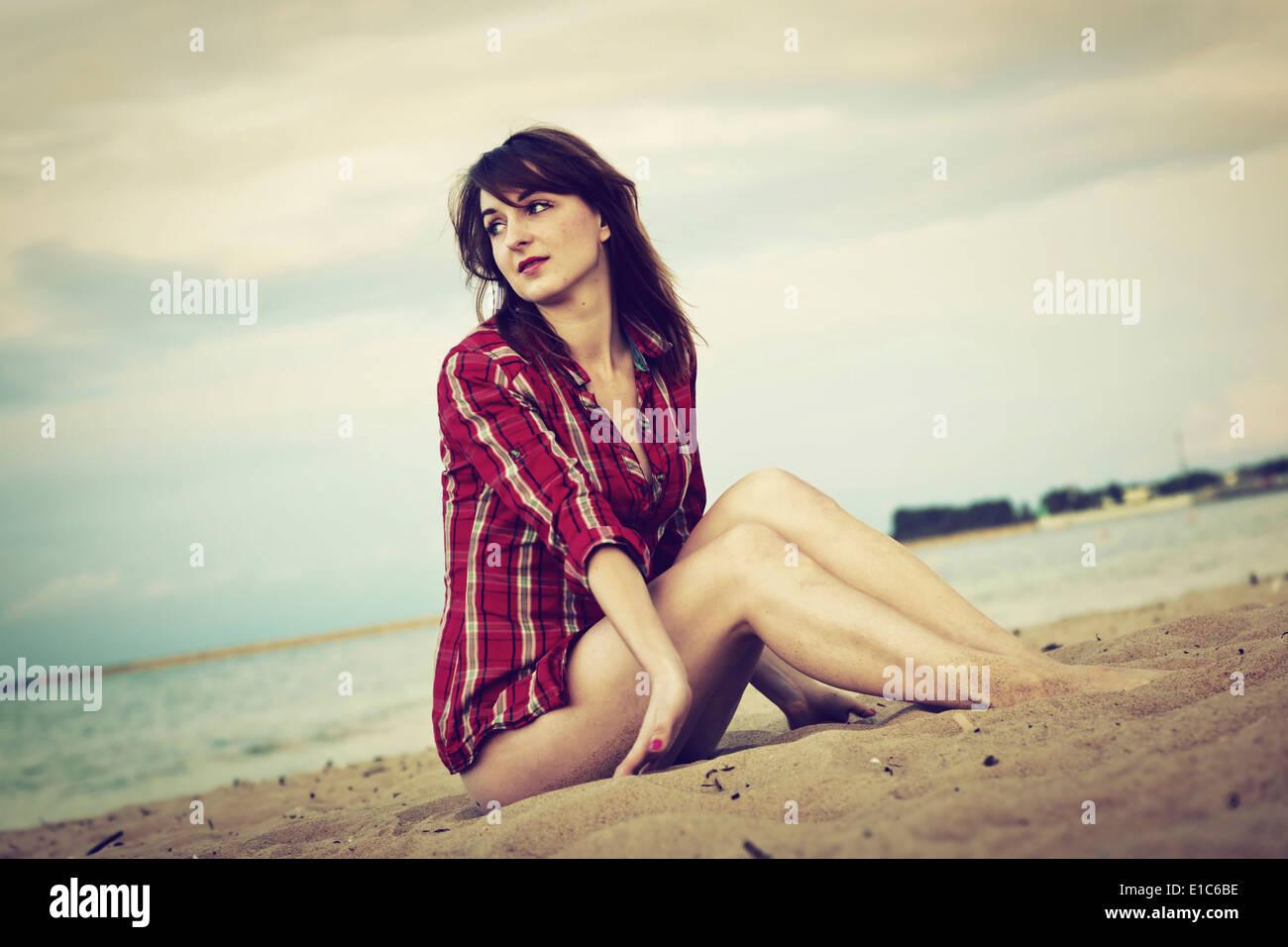 Jeune femme dans une chemise à carreaux rouge détente sur la plage au coucher du soleil Photo Stock
