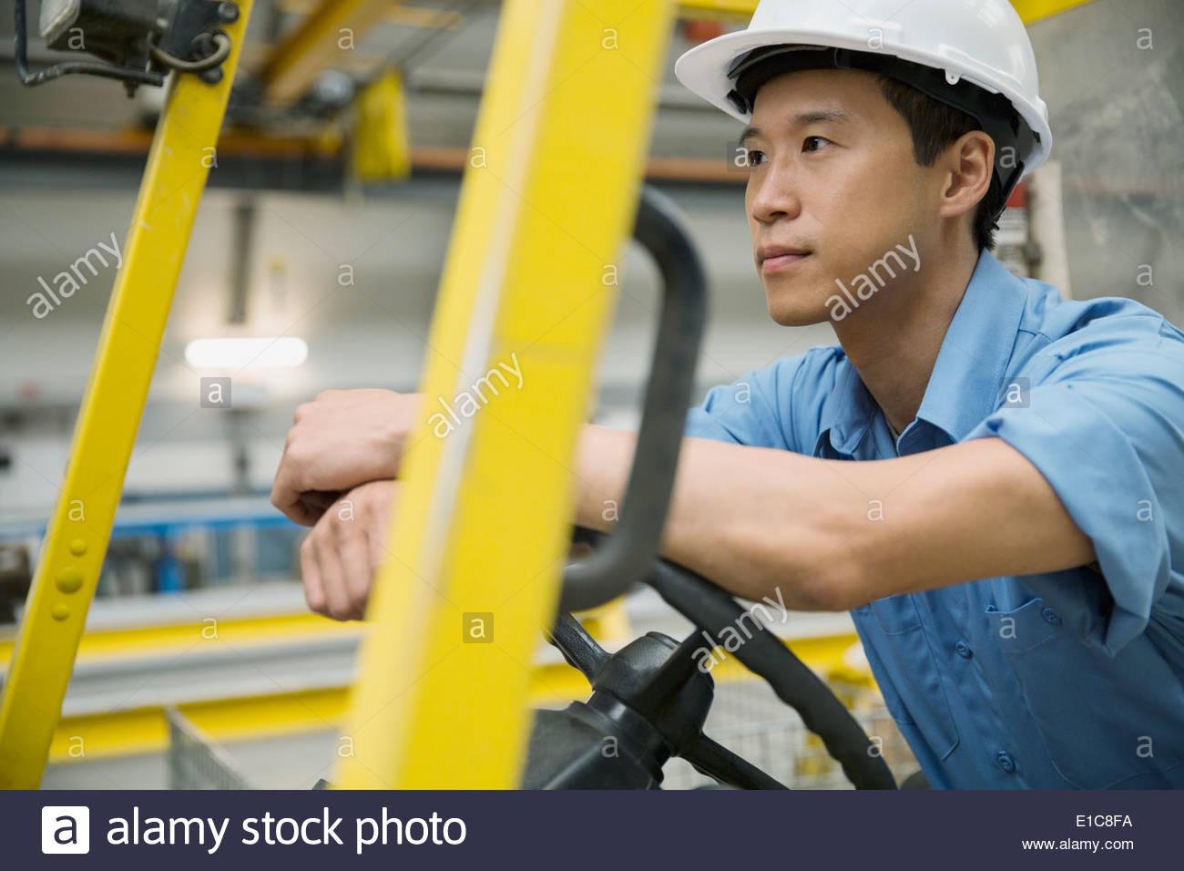 Chariot élévateur d'exploitation travailleur pensif en usine Photo Stock