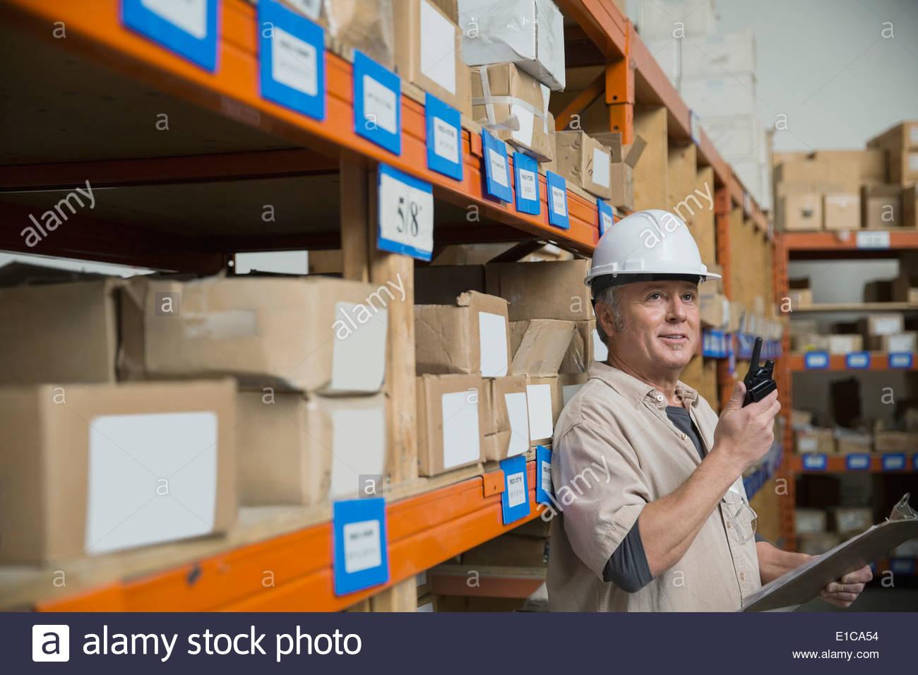Travailleur avec talkie-walkie dans l'entrepôt Photo Stock