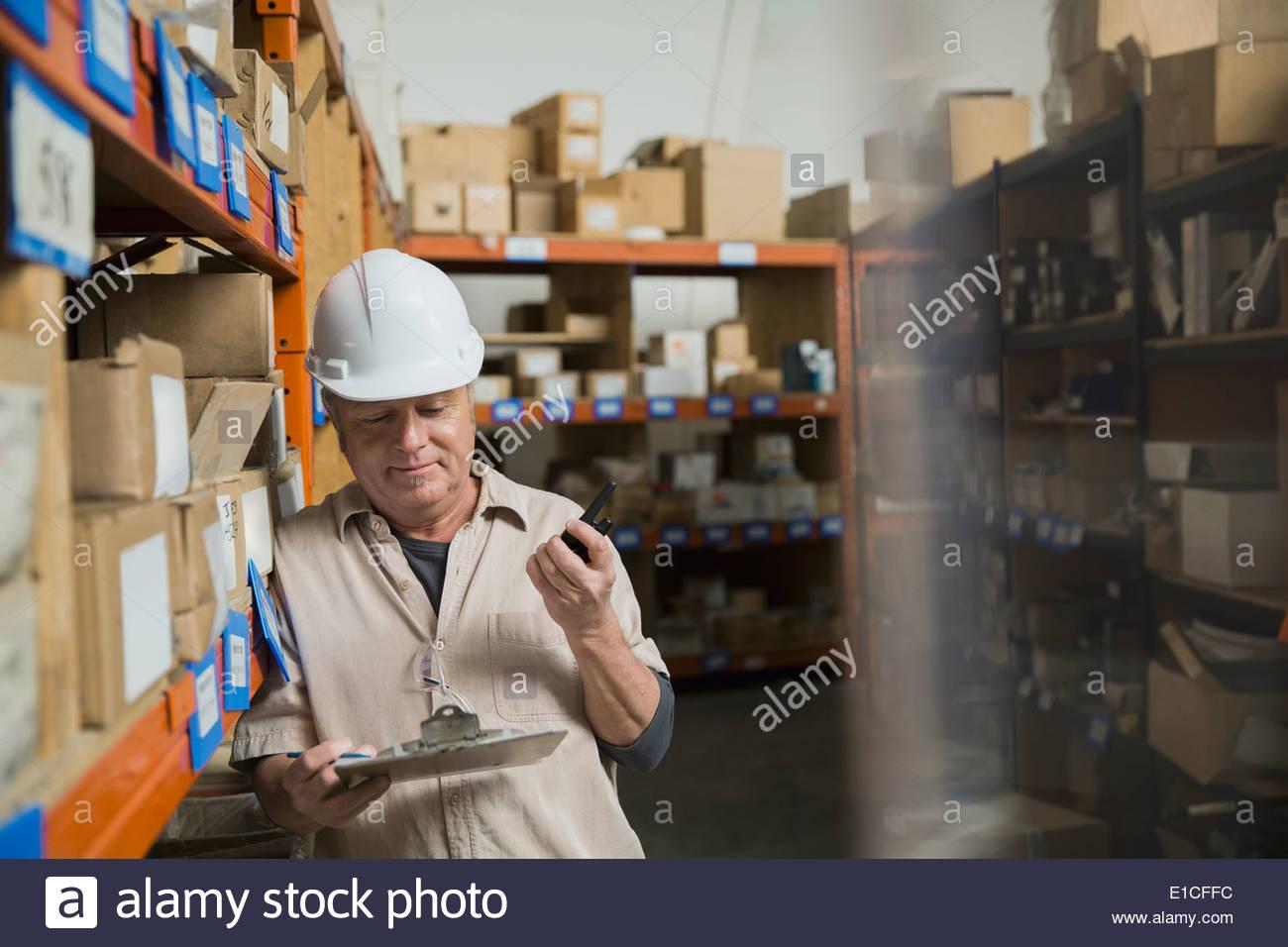 Presse-papiers avec des travailleurs dans l'entrepôt Photo Stock