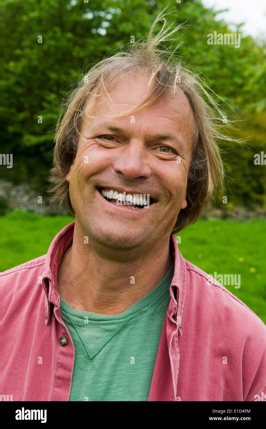 Un homme en vêtements décontractés avec des cheveux blonds, souriant largement. Photo Stock
