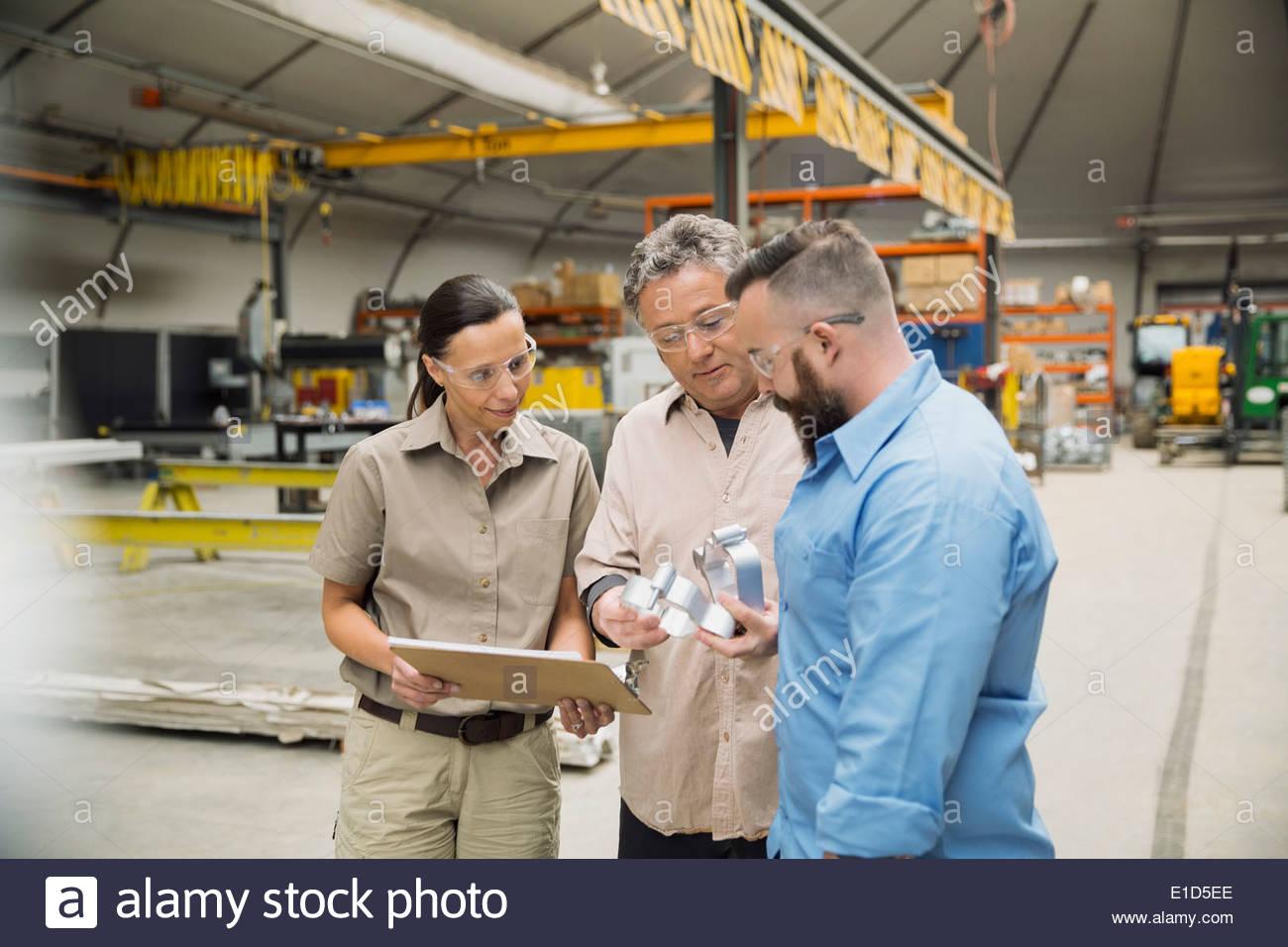 L'examen des travailleurs en usine de fabrication de pièces en métal Photo Stock