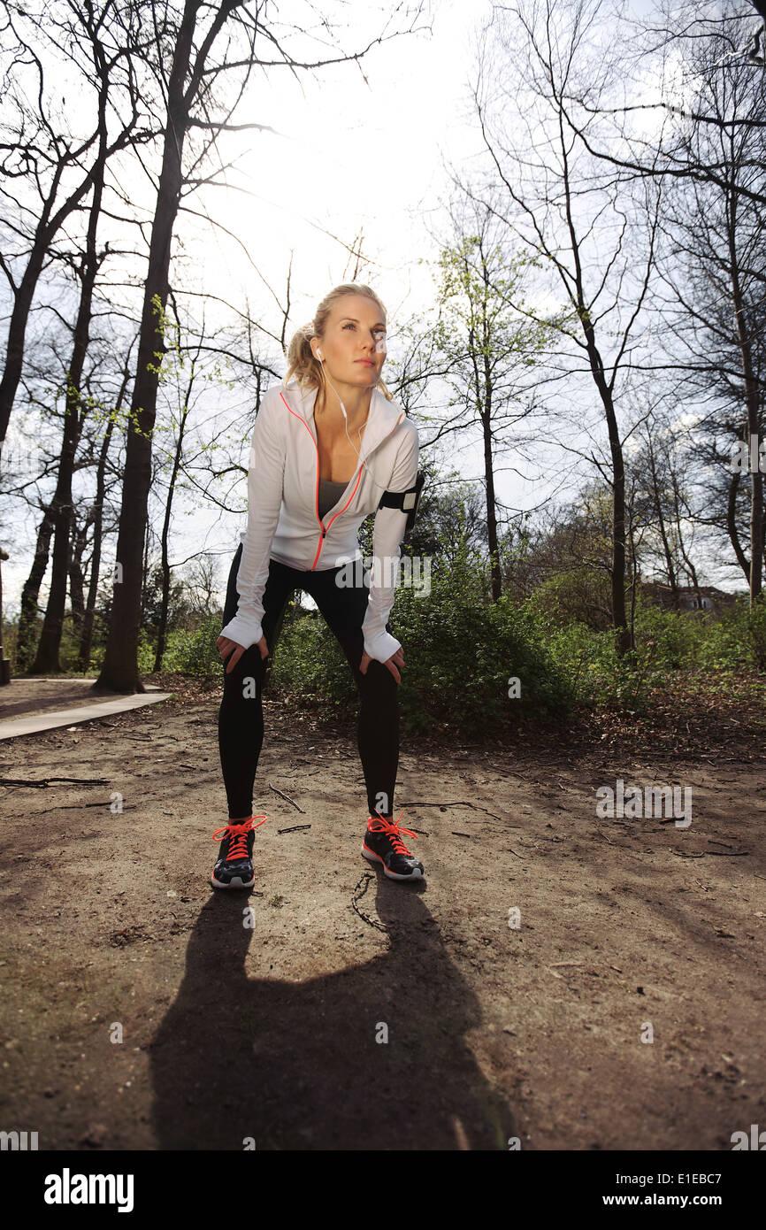 Jeune coureuse d'arrêter pour se reposer. Femme de remise en forme en faisant une pause d'une formation à l'extérieur dans un parc. Photo Stock