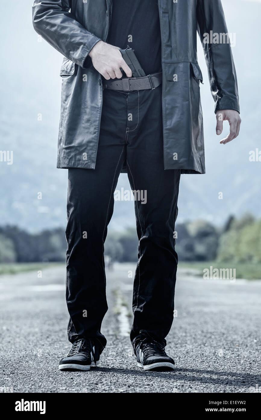 Un homme avec des vêtements noirs et une arme dans son élastique Photo Stock