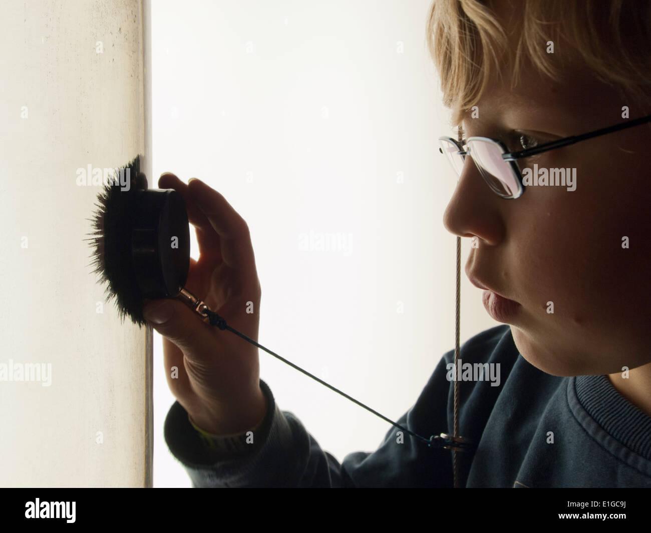 Un garçon de 12 ans est à regarder la limaille de fer dans un réservoir d'eau qui sont attirés par un aimant puissant qui s'est tenue dans la main du garçon Photo Stock