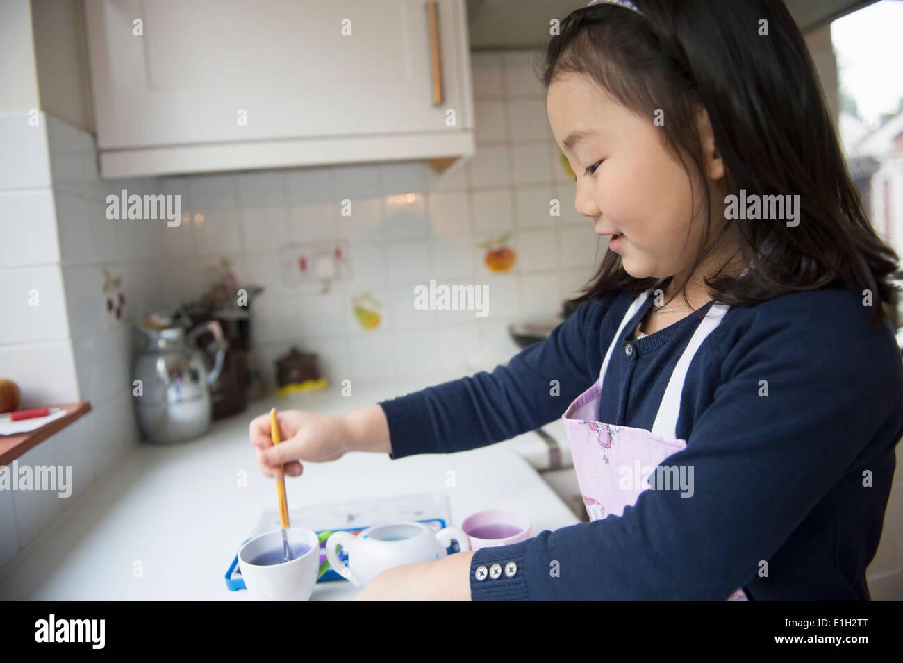 Jeune fille trempant le pinceau dans l'eau dans la cuisine bol Photo Stock