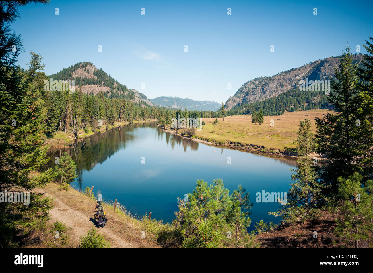 Cycliste homme Rail-Trail dans électrique Valley/chemin de fer de Kettle Valley/sentier KVR next le Kettle Valley River, Colombie-Britannique, Canada Photo Stock