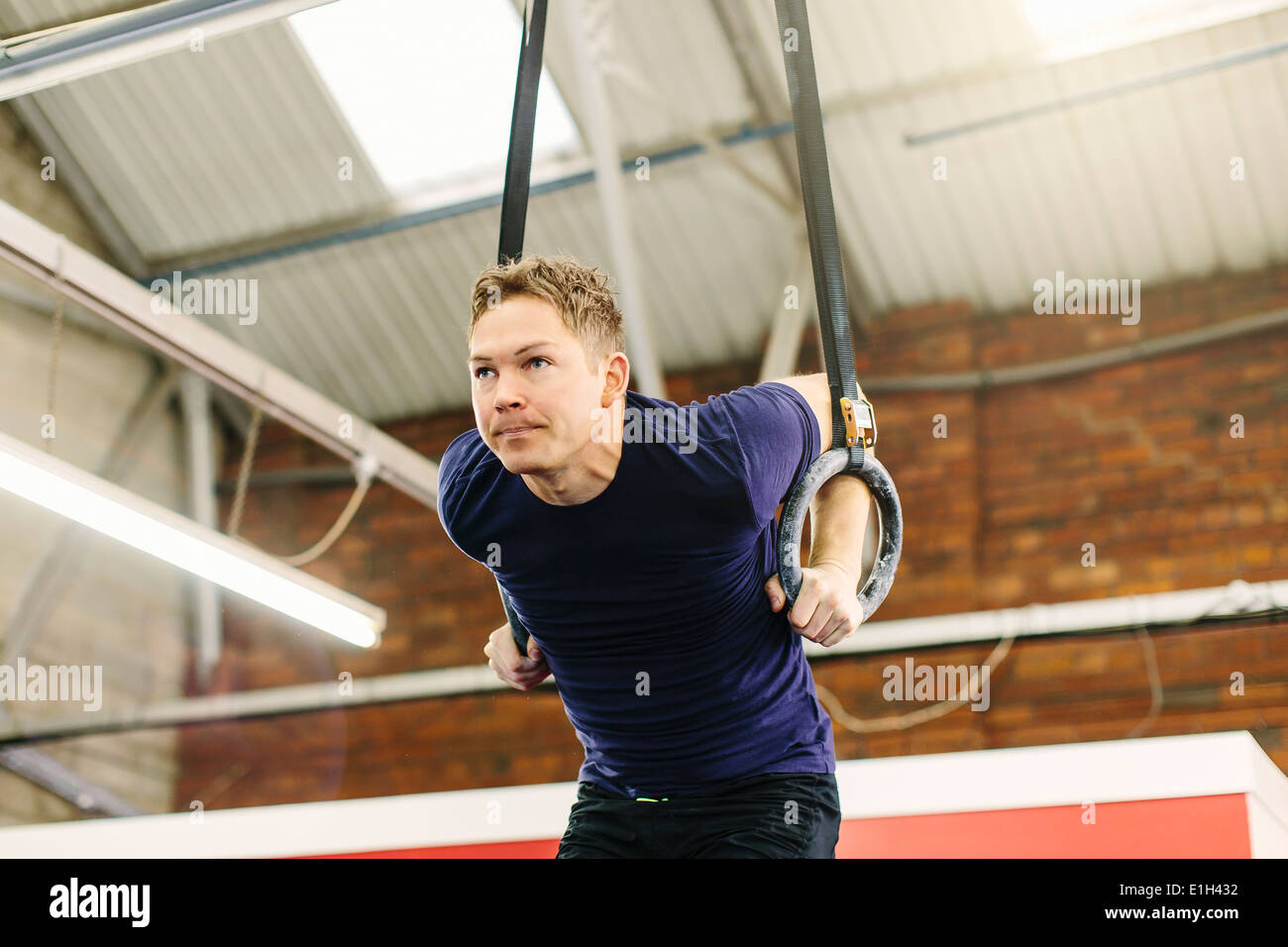 Bagues Homme tirant suspendue in gym Photo Stock