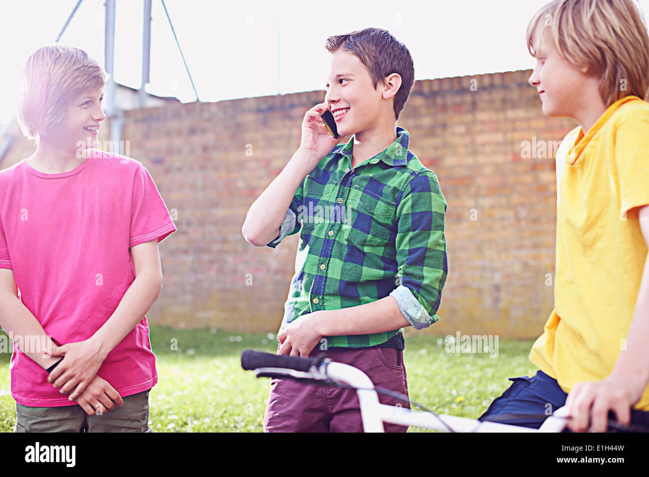 Boy using cell phone avec deux amis Photo Stock