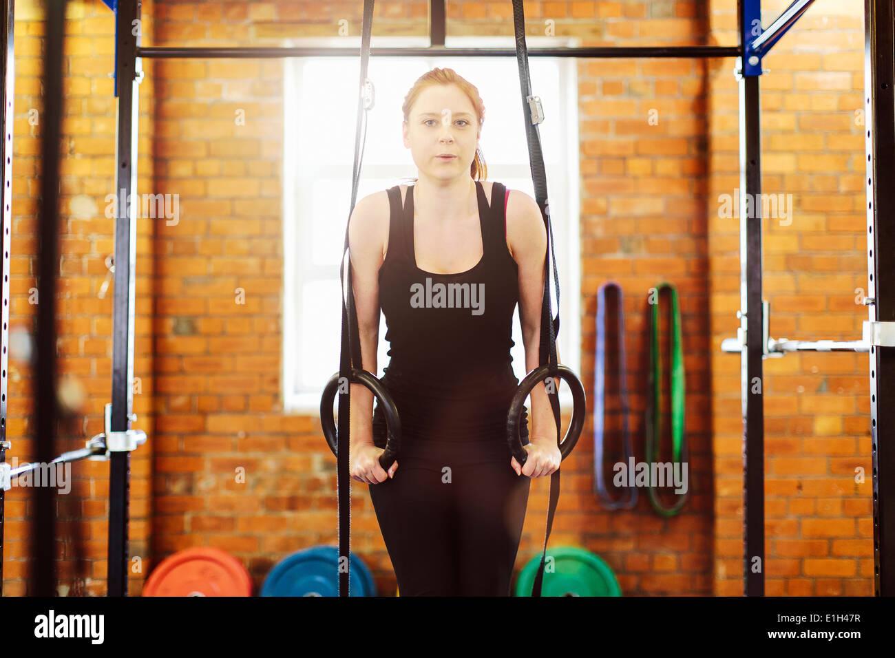 Woman pulling anneaux suspendus dans la salle de sport Photo Stock