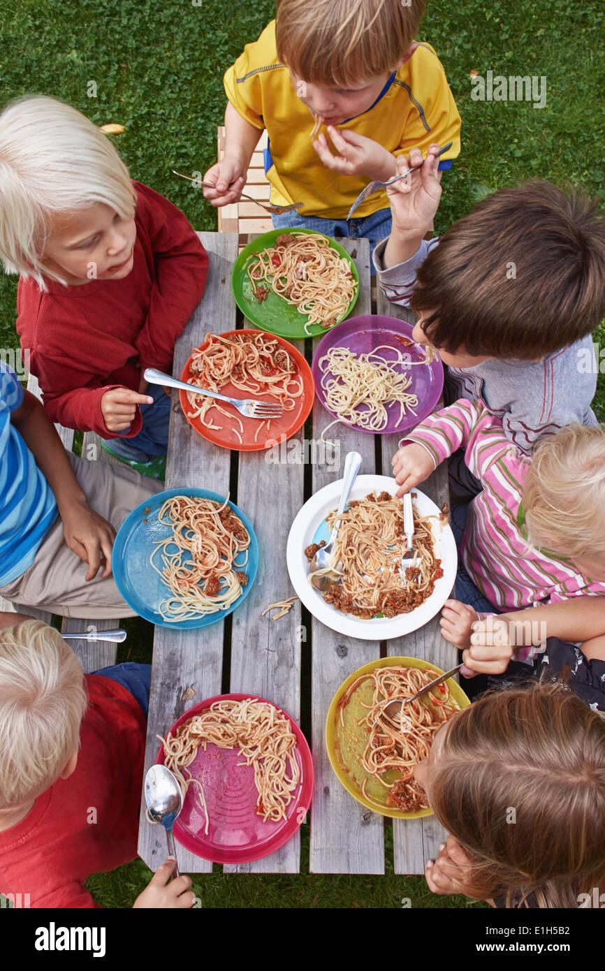 Vue de dessus de sept enfants mange du spaghetti à la table de pique-nique Banque D'Images