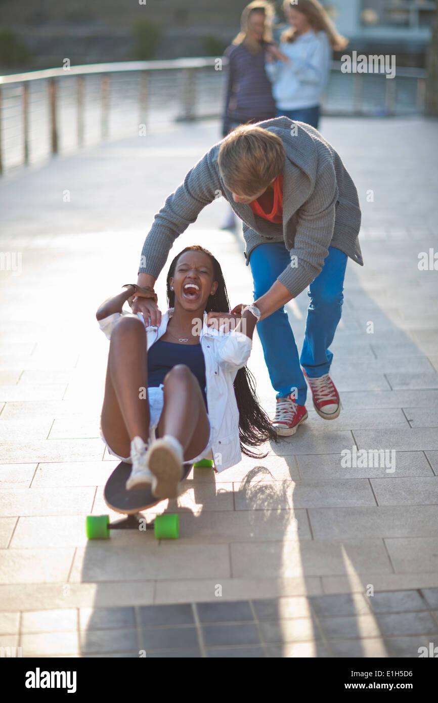 Jeune couple couchait sur planche à Riverside Banque D'Images
