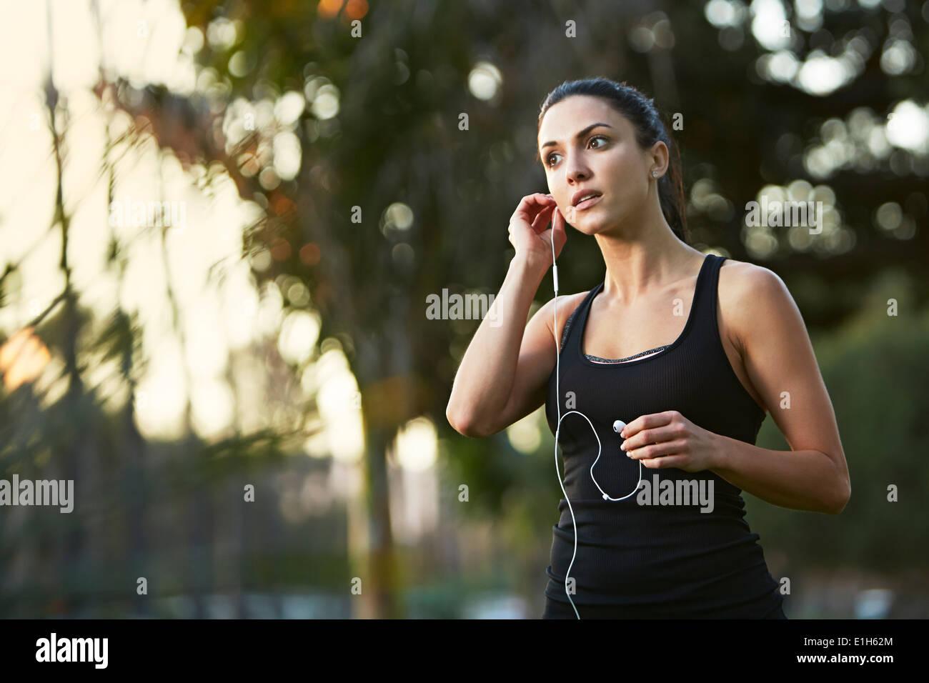 Mid adult woman mettre des écouteurs Photo Stock