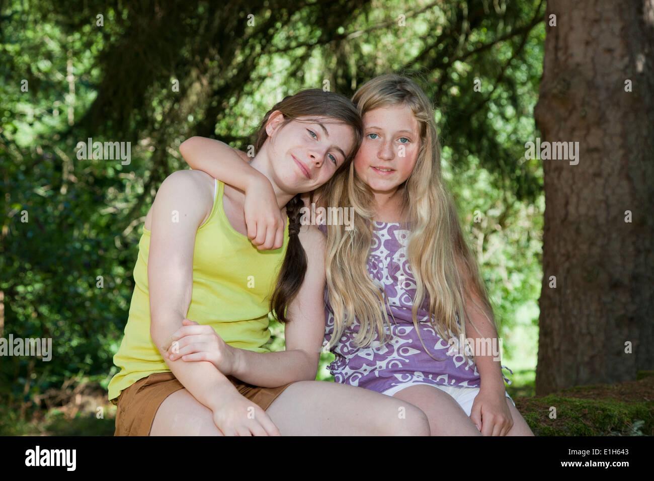 Les adolescents assis dans jardin avec bras autour de Photo Stock