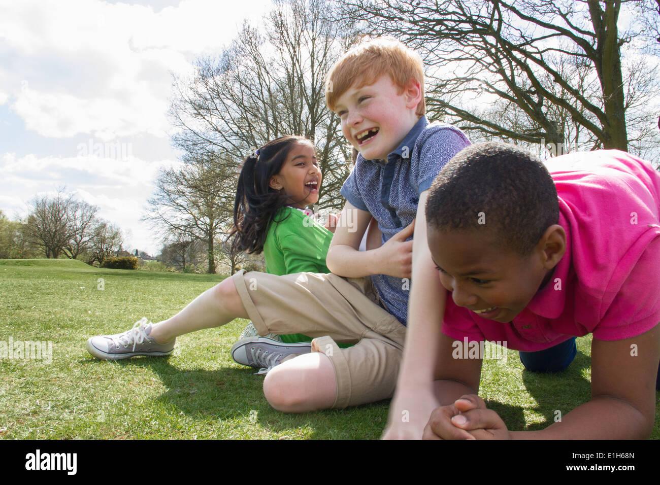 Deux garçons et une fille jouant dans le champ Photo Stock