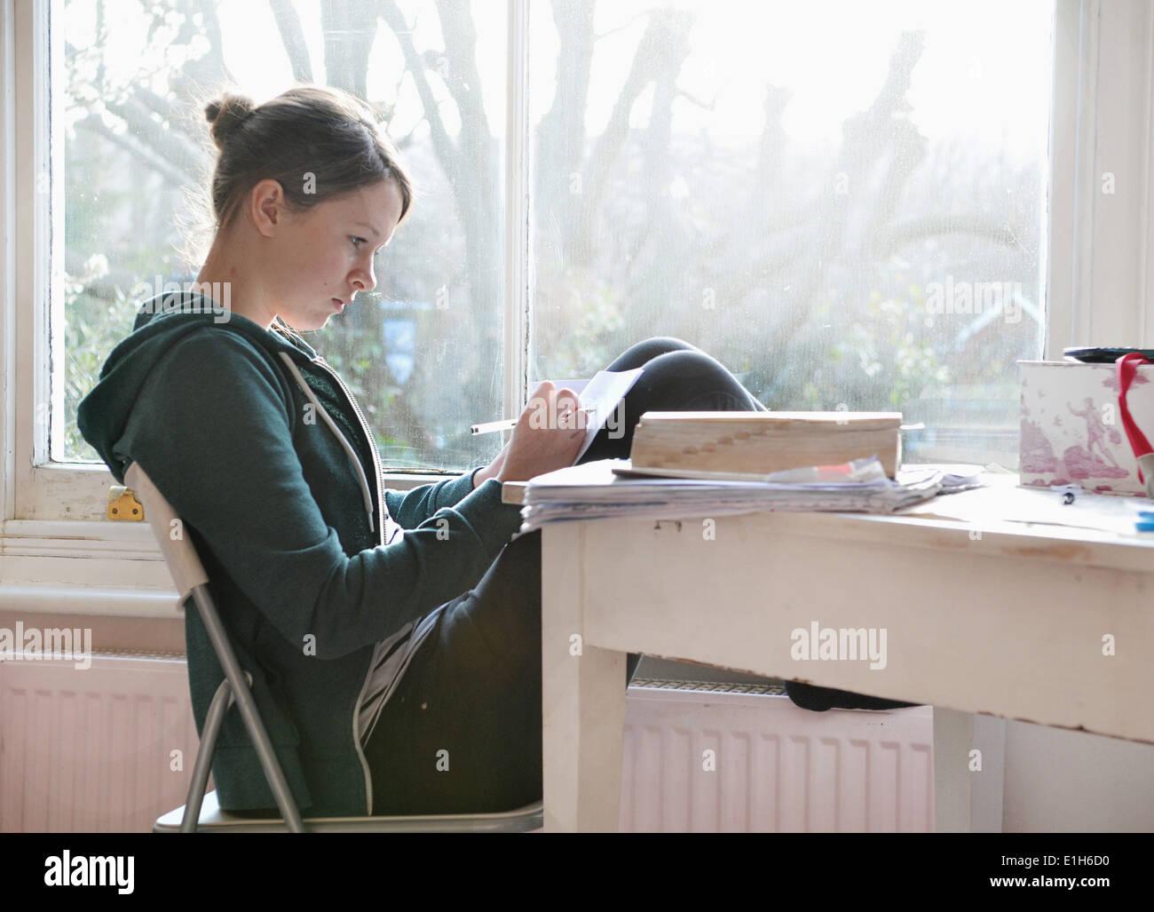 Seize ans, fille, l'étude et la rédaction de notes à côté de fenêtre Banque D'Images
