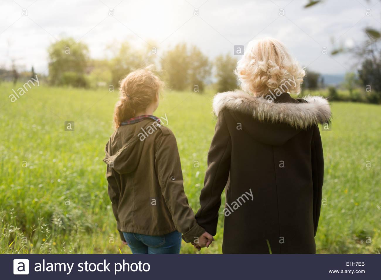 Vue arrière de la mère et fille adolescente holding hands Photo Stock
