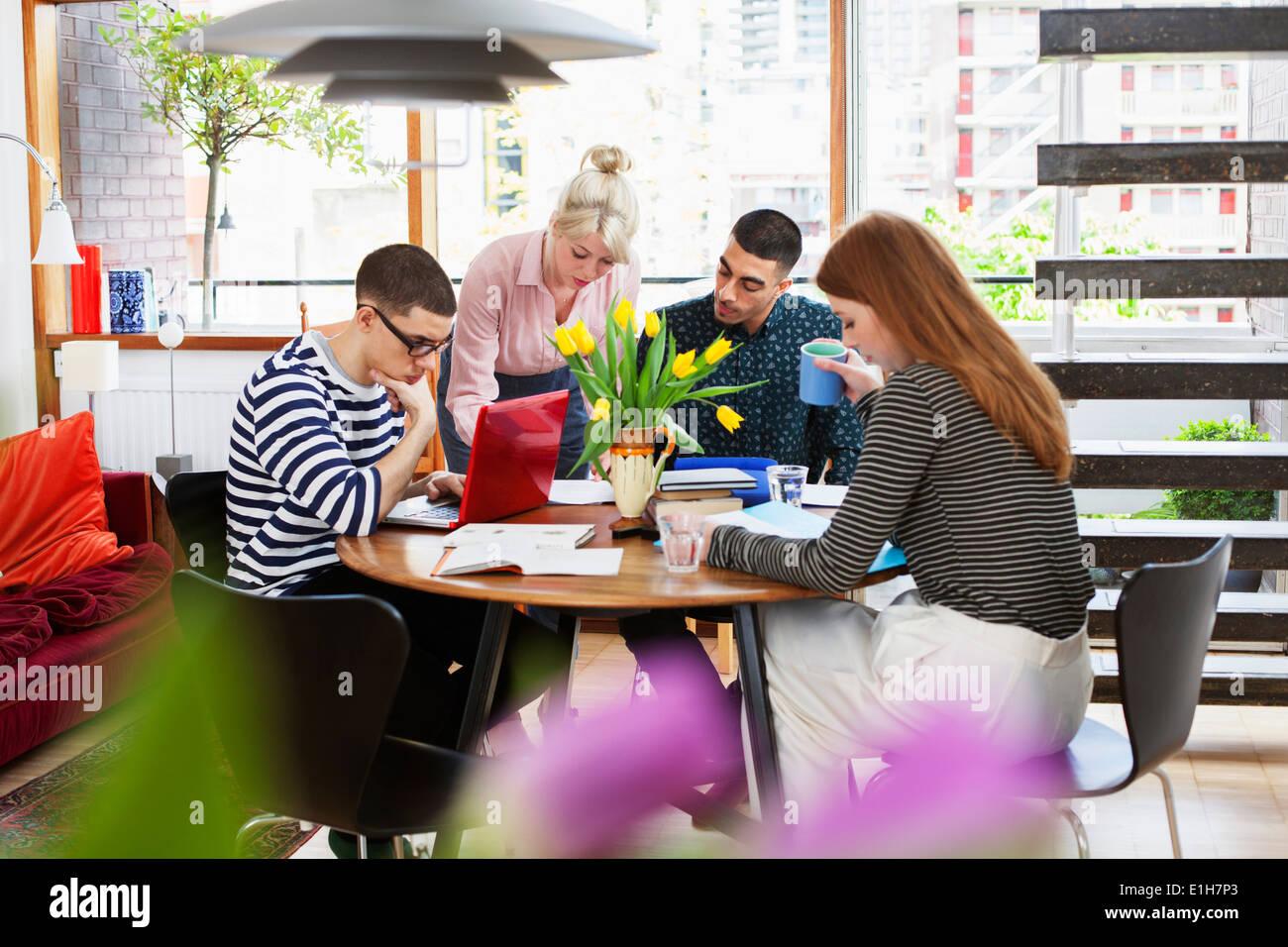 Quatre jeunes adultes assis autour de l'étude table Photo Stock