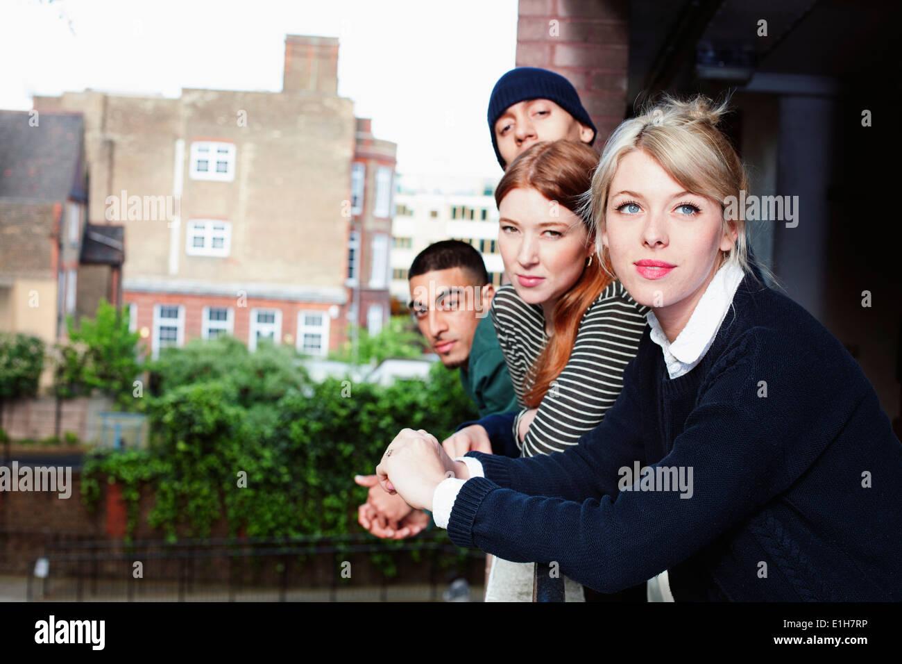 Quatre jeunes adultes, debout sur un balcon dans Londres, Royaume-Uni Photo Stock