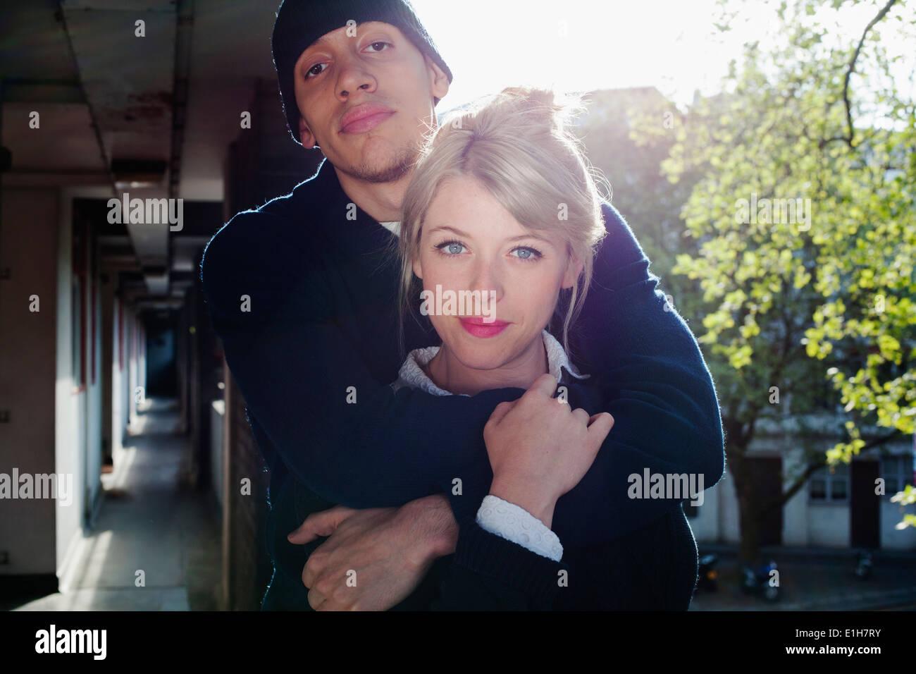 Jeune couple avec bras autour, debout dans le bloc d'appartements, London, UK Photo Stock