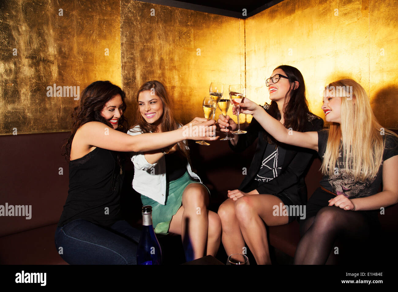 Quatre femmes friends toasting with wine in nightclub Photo Stock