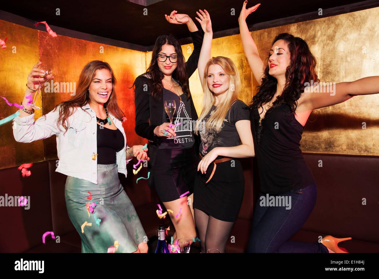 Quatre femmes friends in nightclub Photo Stock
