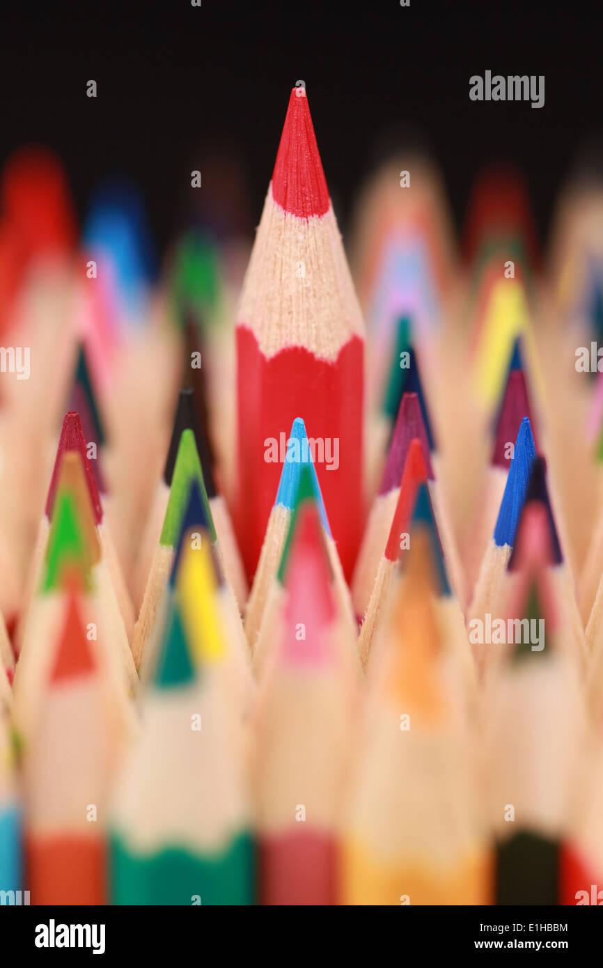 Un crayon rouge se démarquer de la foule. Photo Stock