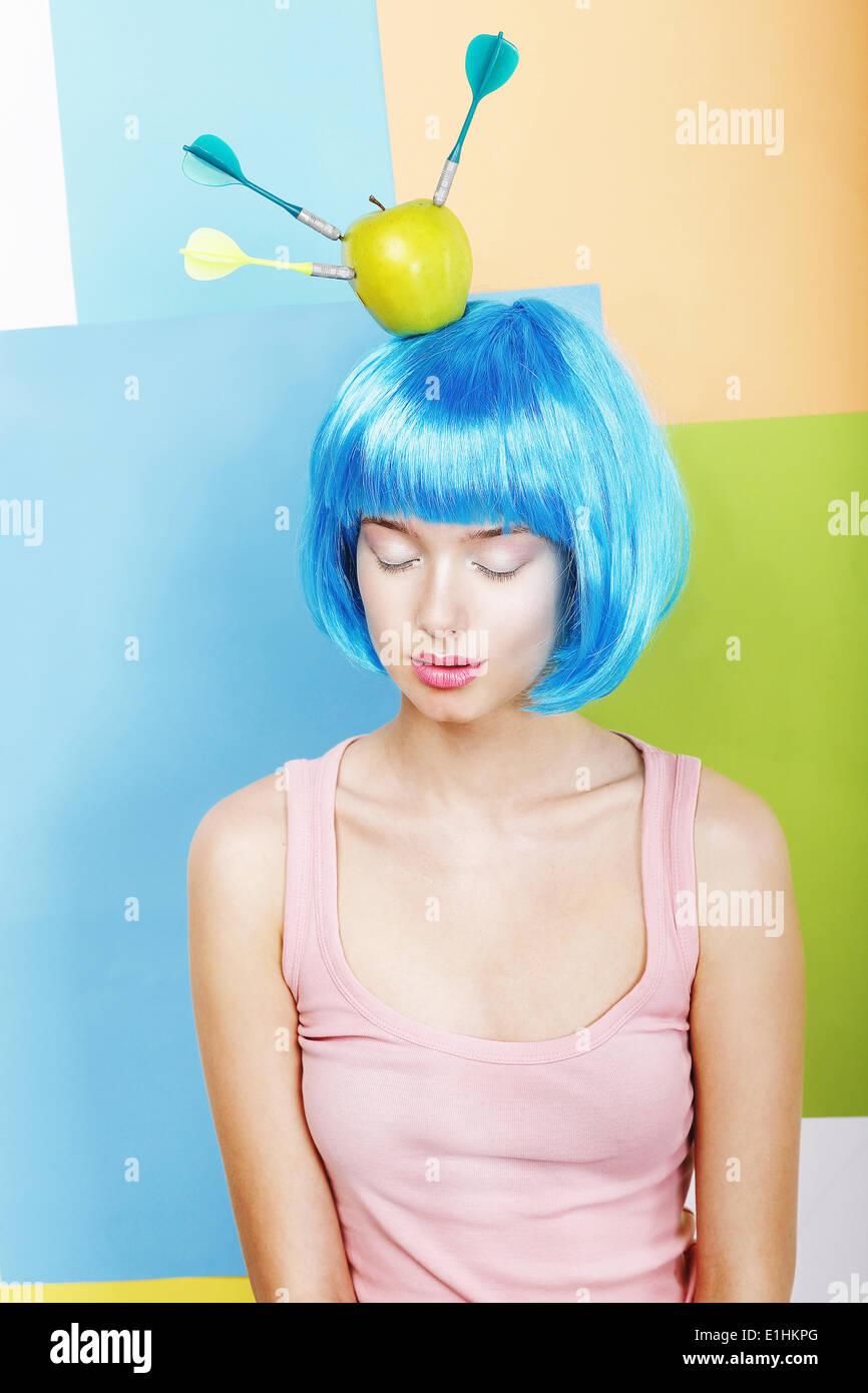 Blague. Femme en bleu EXCENTRIQUE EXCENTRIQUE Perruque avec fléchettes et pomme verte Photo Stock