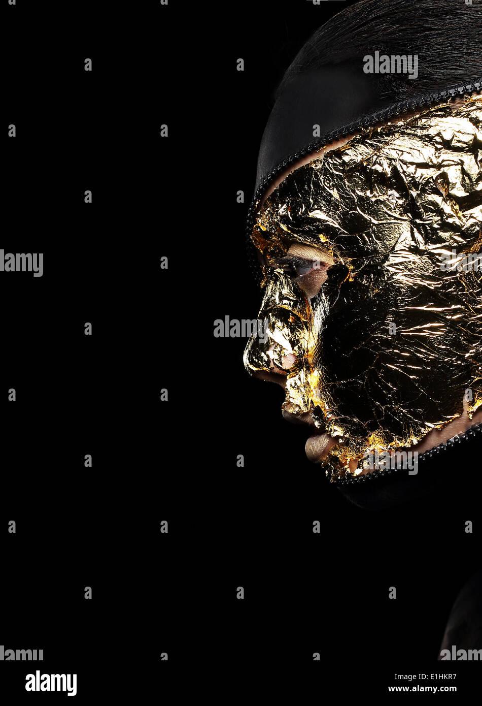 Visage de femme style couverts Golden aluminium sur fond noir. Mystère Photo Stock