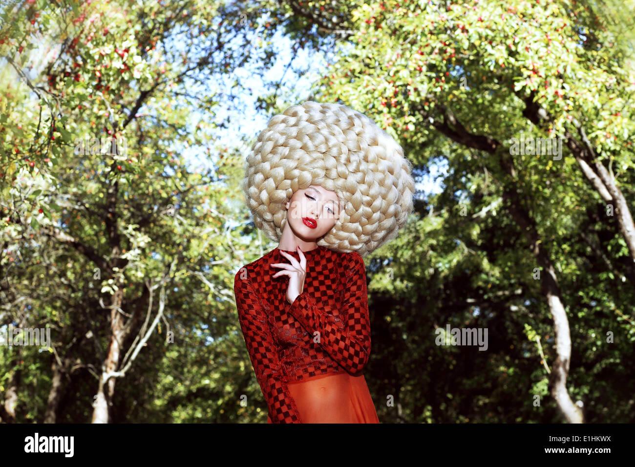 Coiffure extraordinaire. Femme de l'Art somptueux avec perruque de cheveux ondulés Photo Stock