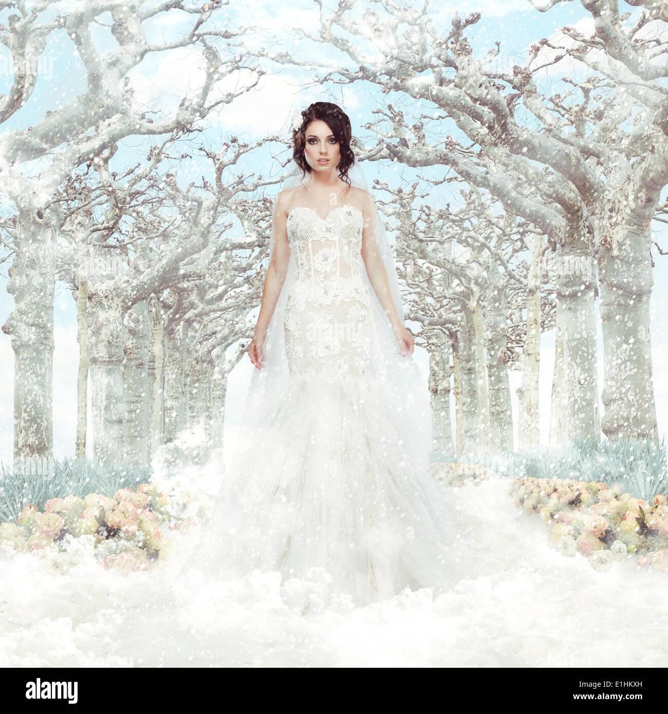 La fantaisie. Le mariage. Mariée en robe blanche sur les arbres et les flocons d'hiver gelé Photo Stock