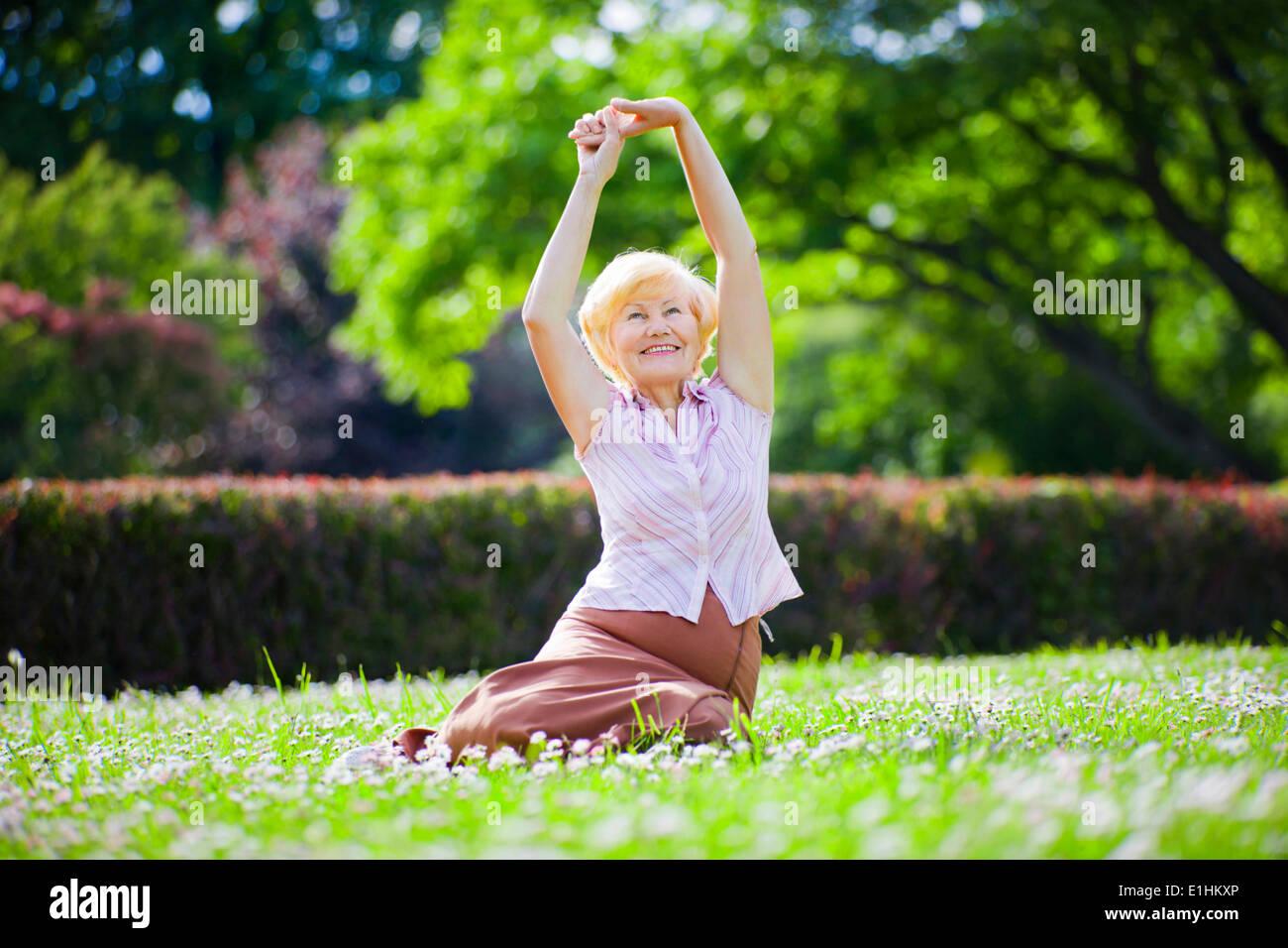 Le bien-être. La santé mentale. Vieille Femme optimiste l'exercice en plein air. Photo Stock