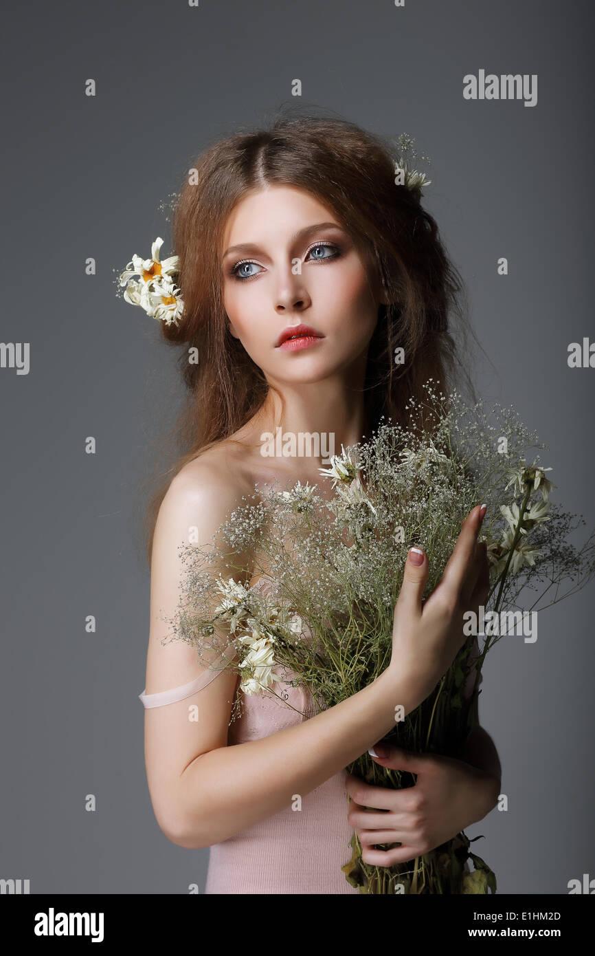 Sentimentalité. Redhaired Muse affectueux avec des fleurs dans les rêves Photo Stock