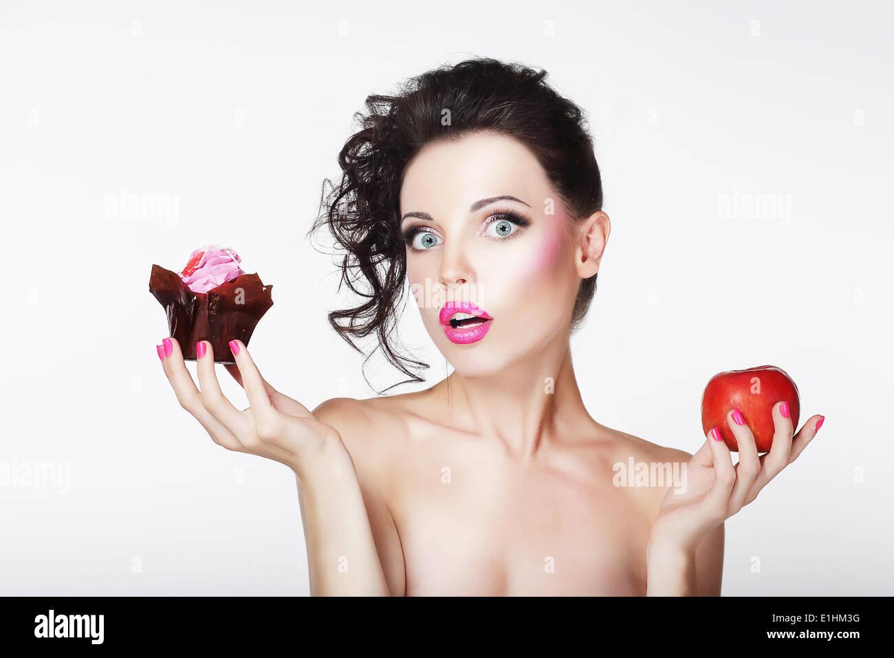 Suivre un régime. Pas sûr abasourdi Girl avoir choisi Apple ou gâteau Photo Stock
