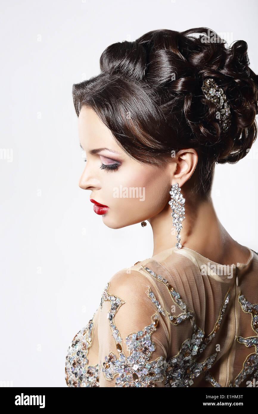 Profil des cheveux bruns chic dame avec les bijoux et la coiffure de fête Photo Stock