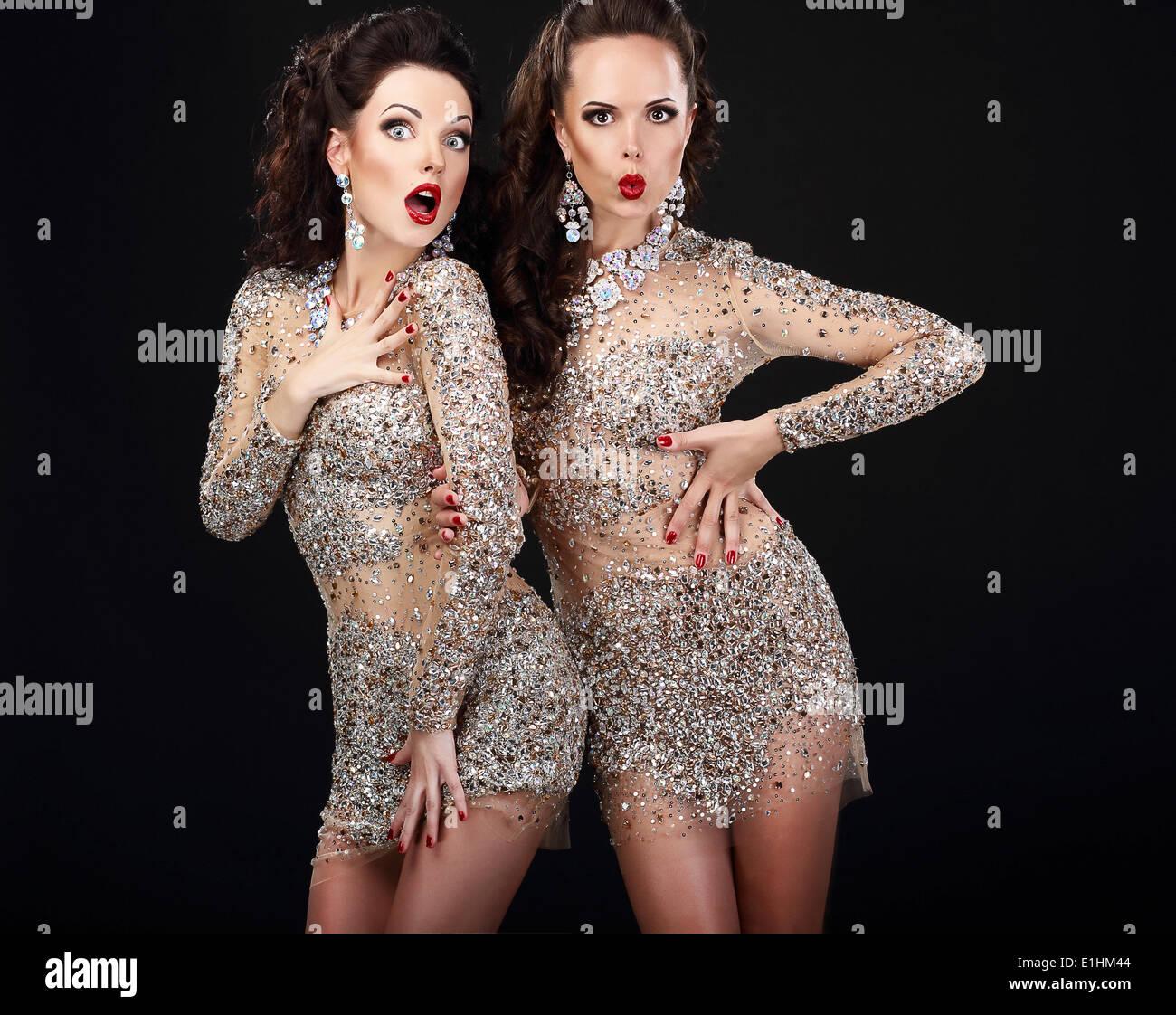 Soiree. Deux jeunes femmes sur fond noir surpris Photo Stock