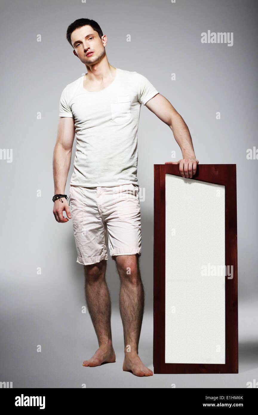 Toute la longueur du jeune homme nu dans un short blanc avec Plackard Photo  Stock 64aaabd54c0