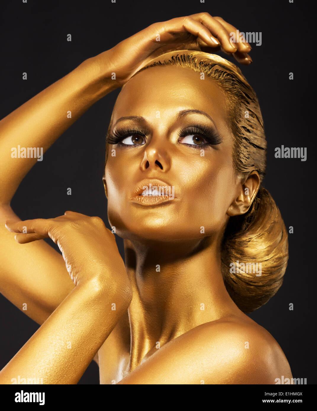 La réflexion. Portrait de femme brillant lumineux avec un miroir d'or. Bodypaint Bronze Photo Stock